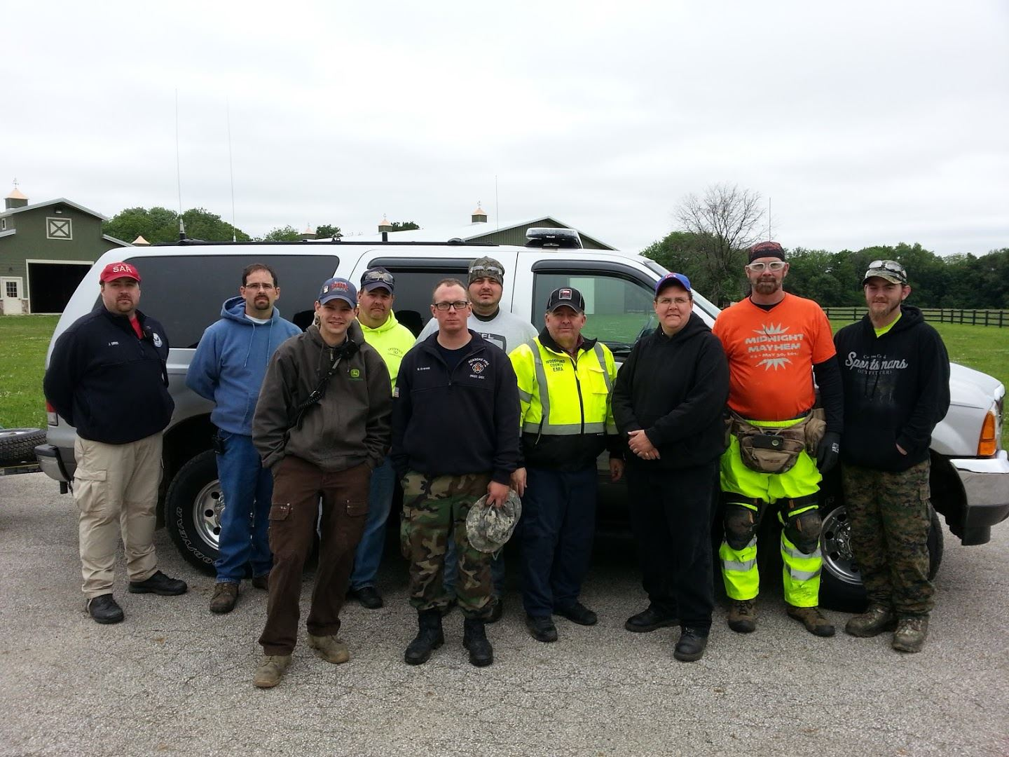 Image of 10 Men of the Search and Rescue Team standing in Front of White SUV