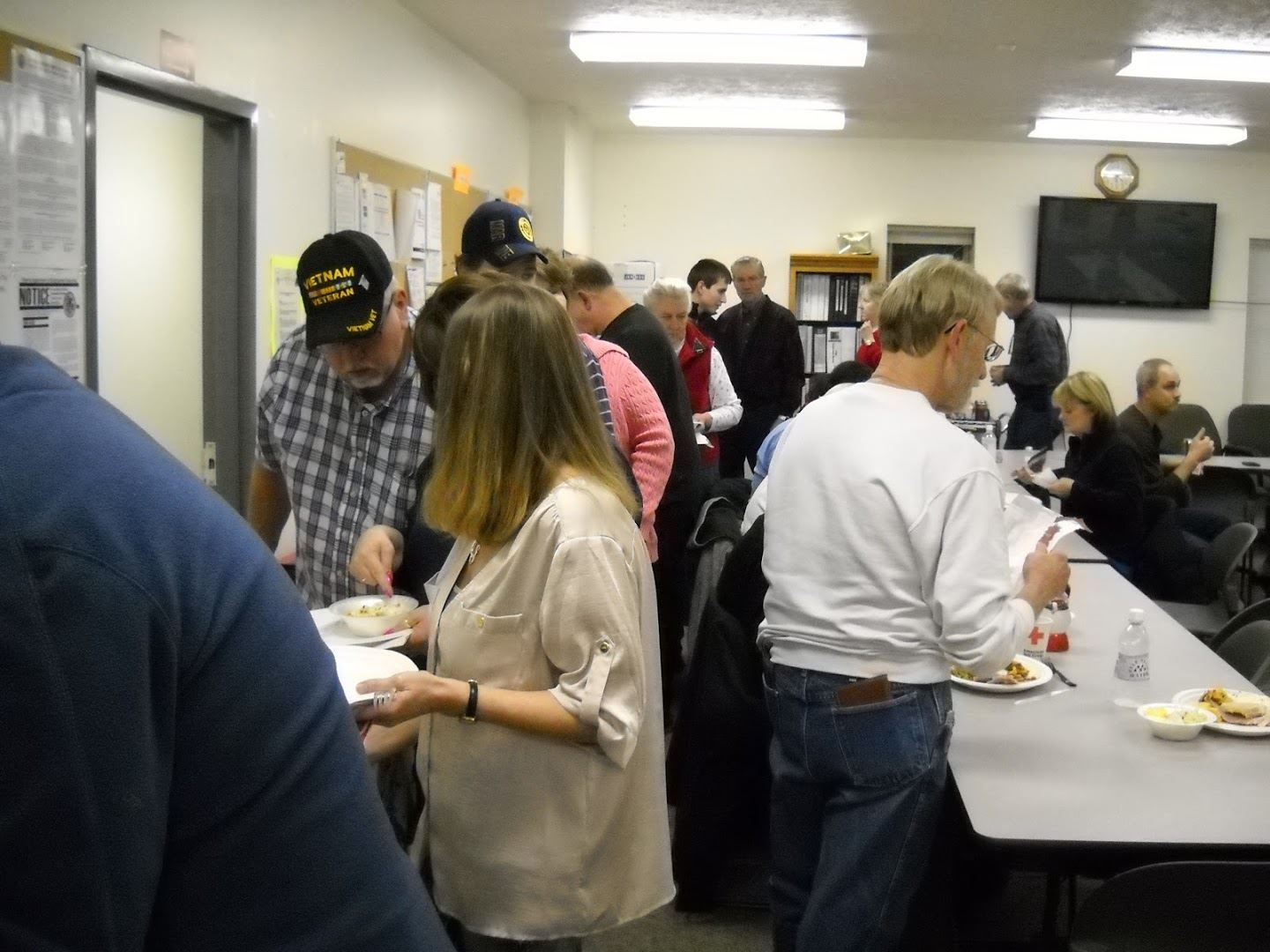 2014 Christmas Potluck, people standing in buffet line serving themselves